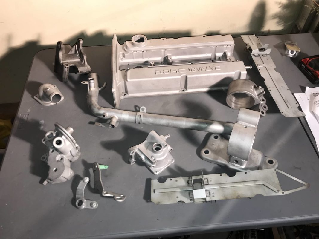 An assortment of engine parts from an Evo 6, after glass beading.